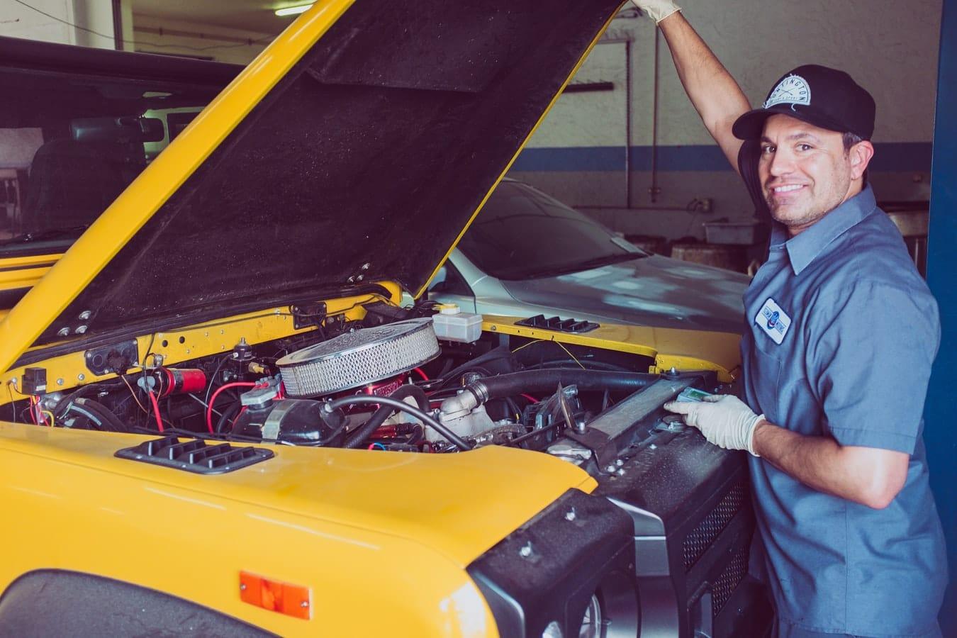 Mécanicien qui inspecte le moteur d'une voiture sous le capot